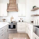 Our white modern farmhouse kitchen with custom wood hood and floating shelves. #...