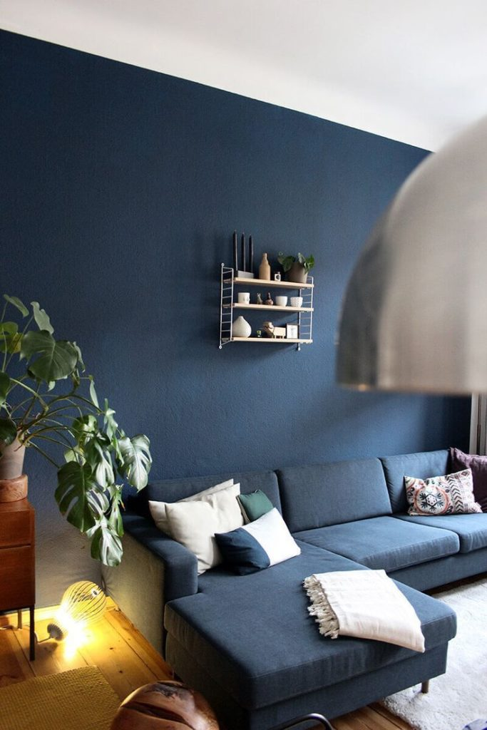 Blue wall in the living room with Midcentury wood and Bolia couch Rooomer.de