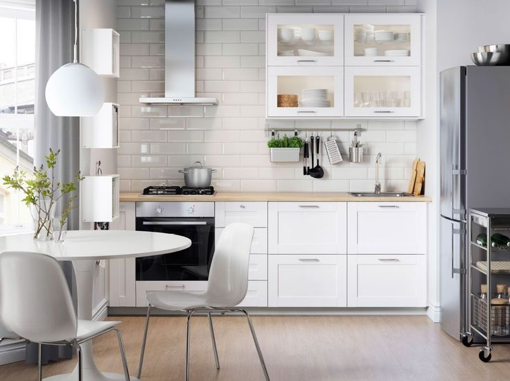 A white kitchen with SÄVEDAL drawer fronts in white and electrical appliances in ...
