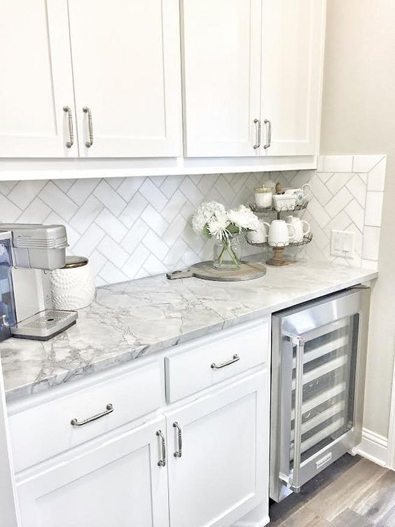 Marble Kitchens with white cabinets and flowers!