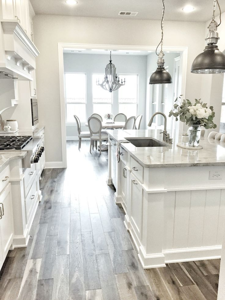 I'm obsessed with this white kitchen! The pendant lights and wood tile floor mak...