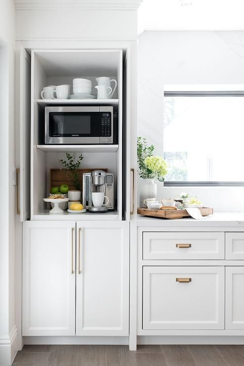 Kitchen coffee station hidden by retractable white cabinet pocket doors. # ...